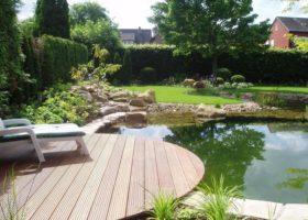 Runde Holzterrasse lädt in Oelde zum Sonnen am Teich ein.