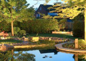 Stimmungsvoll beleuchteter Teich und Garten