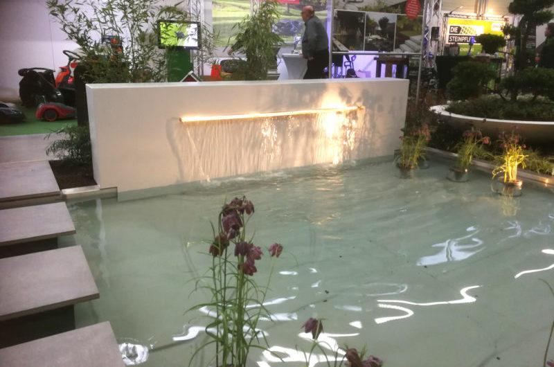 Baumesse Münster, weiße Designwand mit breiter Wasserschütte